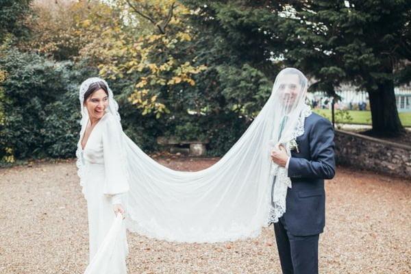 le marié hilare portant sur la tête le voile de la mariée