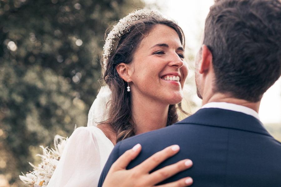 mariée souriant à son mari dans ses bras