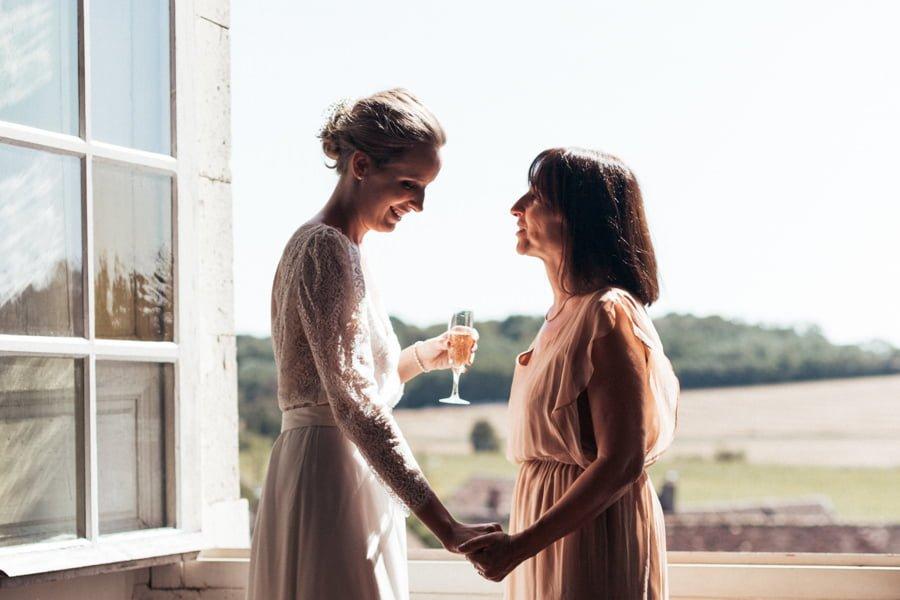mariée et sa mère se tenant la main le matin du mariage