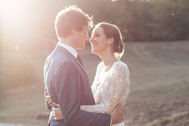 des mariés sur le point de s'embrasser au coucher du soleil