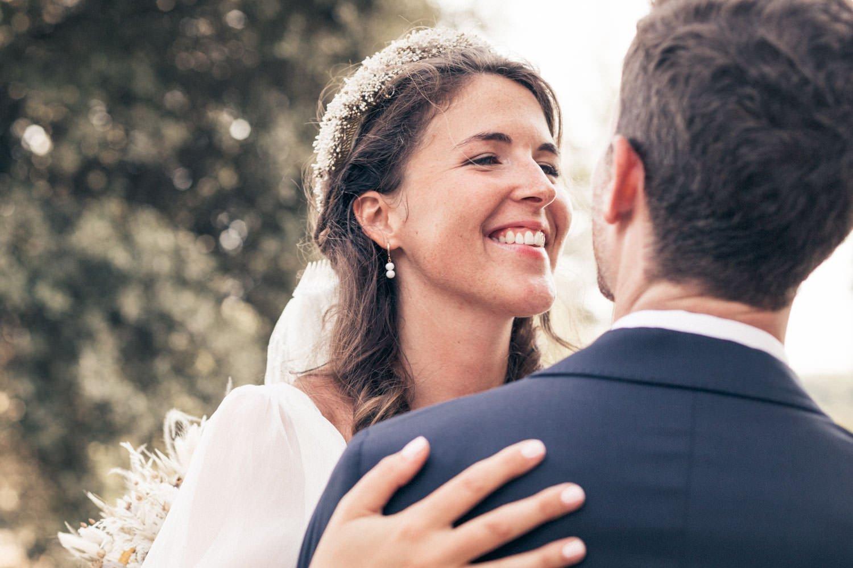 une mariée souriant à son mari en le serrant dans les bras